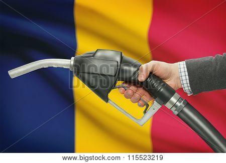Fuel Pump Nozzle In Hand With National Flag On Background - Chad