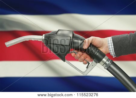 Fuel Pump Nozzle In Hand With National Flag On Background - Costa Rica