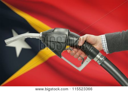 Fuel Pump Nozzle In Hand With National Flag On Background - East Timor