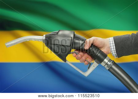 Fuel Pump Nozzle In Hand With National Flag On Background - Gabon