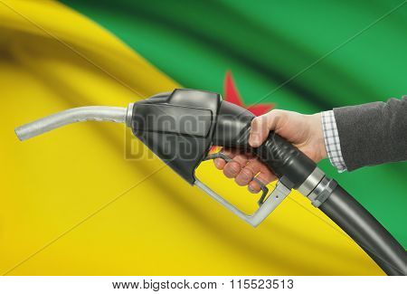 Fuel Pump Nozzle In Hand With National Flag On Background - French Guiana