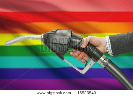 Fuel Pump Nozzle In Hand With National Flag On Background - Lgbt People