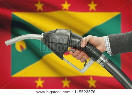 Fuel Pump Nozzle In Hand With National Flag On Background - Grenada