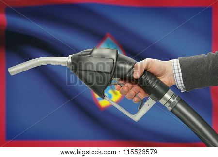 Fuel Pump Nozzle In Hand With National Flag On Background - Guam
