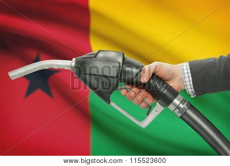 Fuel Pump Nozzle In Hand With National Flag On Background - Guinea-bissau