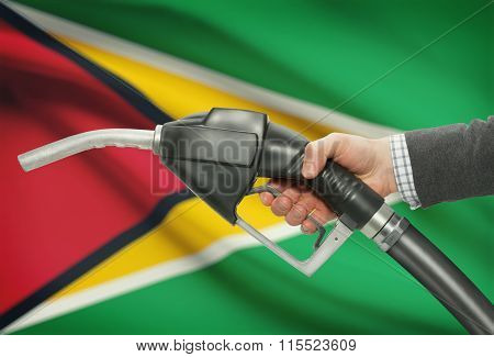 Fuel Pump Nozzle In Hand With National Flag On Background - Guyana