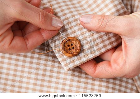 Woman Hands Sewing Button On Fabric