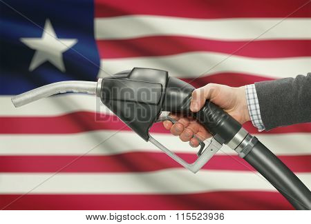 Fuel Pump Nozzle In Hand With National Flag On Background - Liberia