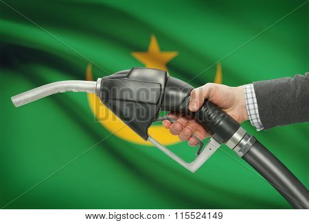 Fuel Pump Nozzle In Hand With National Flag On Background - Mauritania