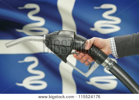 Fuel Pump Nozzle In Hand With National Flag On Background - Martinique