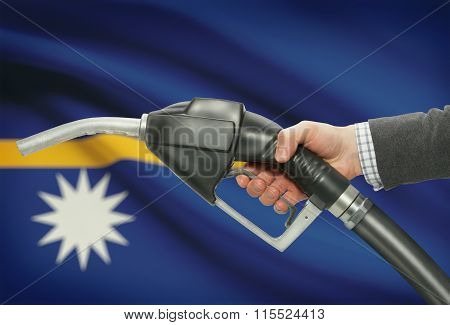 Fuel Pump Nozzle In Hand With National Flag On Background - Nauru