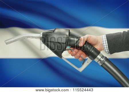 Fuel Pump Nozzle In Hand With National Flag On Background - Nicaragua