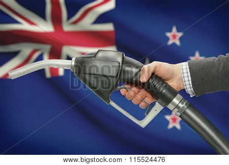Fuel Pump Nozzle In Hand With National Flag On Background - New Zealand