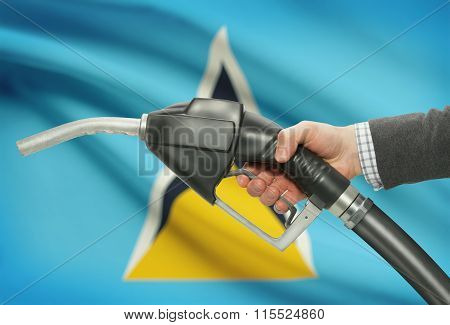 Fuel Pump Nozzle In Hand With National Flag On Background - Saint Lucia