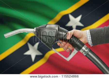 Fuel Pump Nozzle In Hand With National Flag On Background - Saint Kitts And Nevis