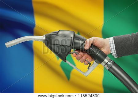 Fuel Pump Nozzle In Hand With National Flag On Background - Saint Vincent And The Grenadines