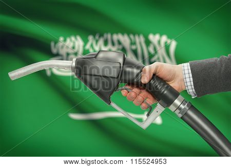 Fuel Pump Nozzle In Hand With National Flag On Background - Saudi Arabia