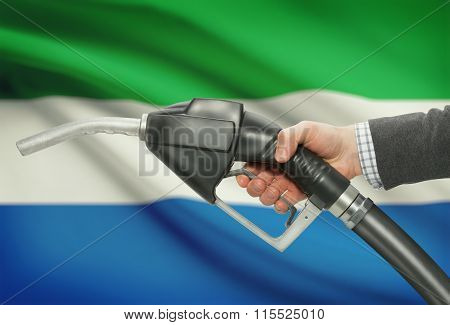 Fuel Pump Nozzle In Hand With National Flag On Background - Sierra Leone