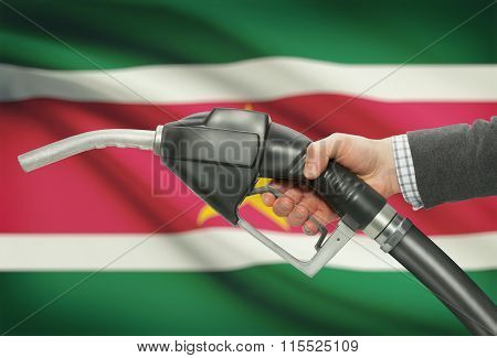 Fuel Pump Nozzle In Hand With National Flag On Background - Suriname