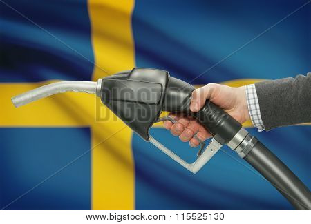 Fuel Pump Nozzle In Hand With National Flag On Background - Sweden
