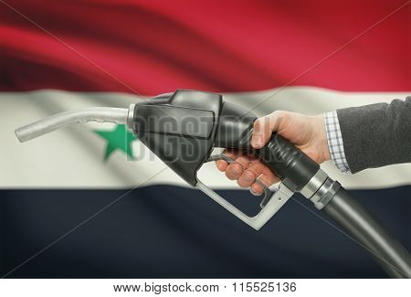 Fuel Pump Nozzle In Hand With National Flag On Background - Syria