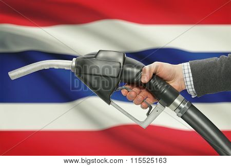 Fuel Pump Nozzle In Hand With National Flag On Background - Thailand