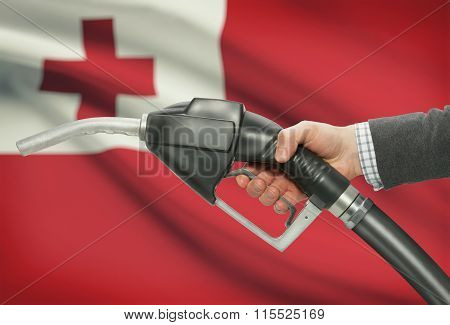 Fuel Pump Nozzle In Hand With National Flag On Background - Tonga