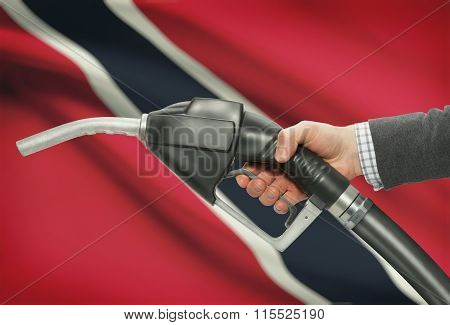Fuel Pump Nozzle In Hand With National Flag On Background - Trinidad And Tobago
