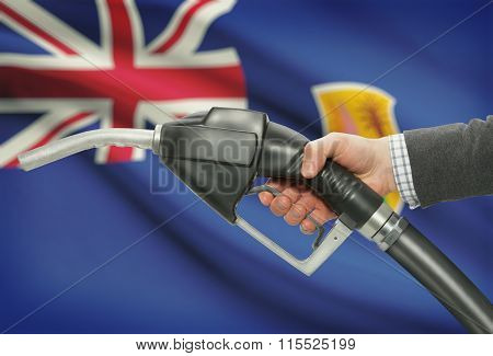 Fuel Pump Nozzle In Hand With National Flag On Background - Turks And Caicos Islands