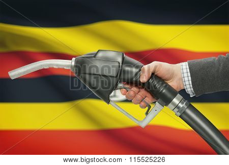 Fuel Pump Nozzle In Hand With National Flag On Background - Uganda
