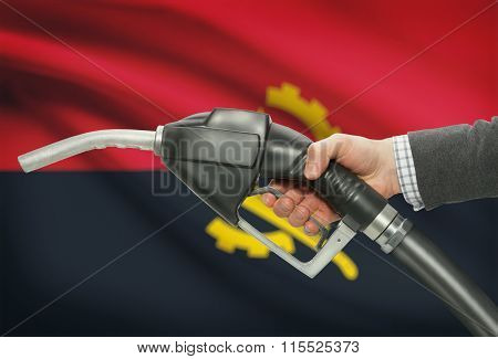 Fuel Pump Nozzle In Hand With National Flag On Background - Angola