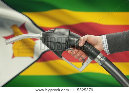 Fuel Pump Nozzle In Hand With National Flag On Background - Zimbabwe