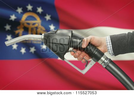 Fuel Pump Nozzle In Hand With Usa States Flags On Background - Georgia