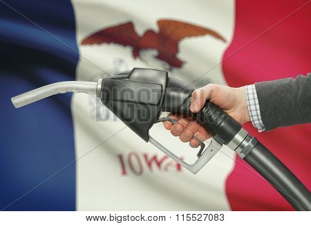 Fuel Pump Nozzle In Hand With Usa States Flags On Background - Iowa