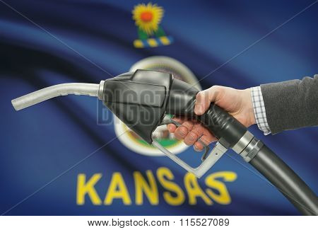 Fuel Pump Nozzle In Hand With Usa States Flags On Background - Kansas