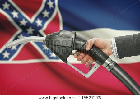 Fuel Pump Nozzle In Hand With Usa States Flags On Background - Mississippi