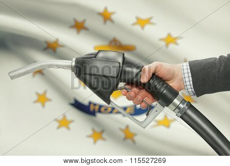 Fuel Pump Nozzle In Hand With Usa States Flags On Background - Rhode Island