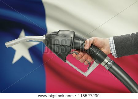 Fuel Pump Nozzle In Hand With Usa States Flags On Background - Texas