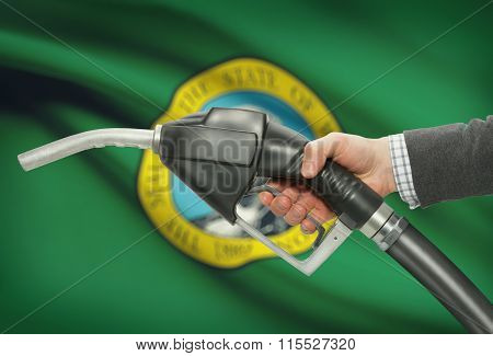 Fuel Pump Nozzle In Hand With Usa States Flags On Background - Washington