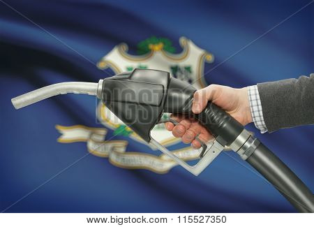 Fuel Pump Nozzle In Hand With Usa States Flags On Background - Connecticut