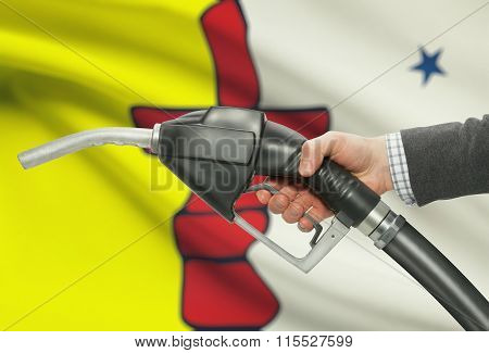 Fuel Pump Nozzle In Hand With Canadian Provinces Flags On Background - Nunavut