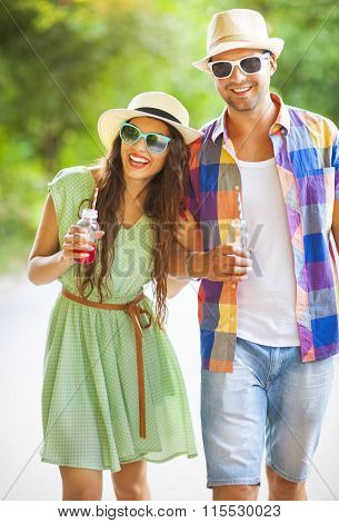 Happy Young Couple Drinking Juice And Walking