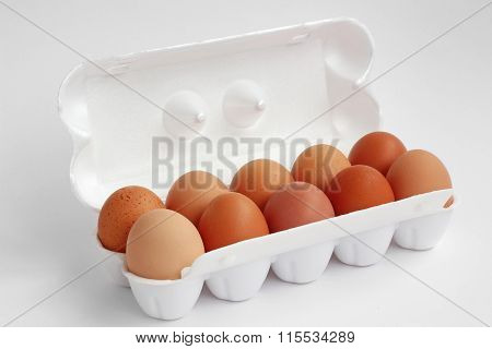 Ten Chicken Brown Eggs In White Packing On A White Background.