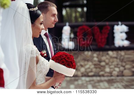 Bride And Groom Near And Riginal Romantic Valentyne Flower Sign The Word Love Spelled With White And