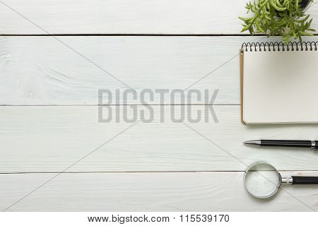 Office desk table with supplies. Top view. Copy space for text. Notepad, pen, magnifying glass, flow