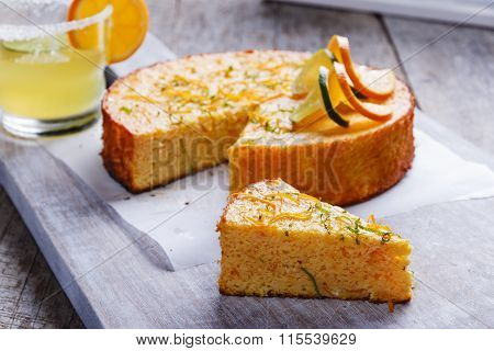 Home made whole testy orange cake on a wooden surface