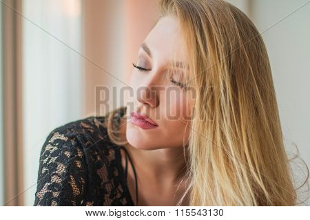 Close up portrait of beautiful young blonde woman in black lace shirt,eyes closed, sitting next to w