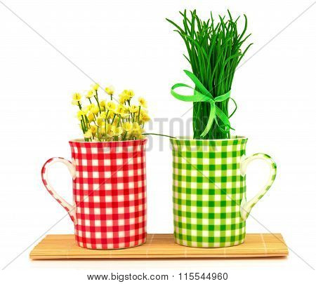 Green And Red Cups With Spring Flowers And Grass With Ribbon On The Mat
