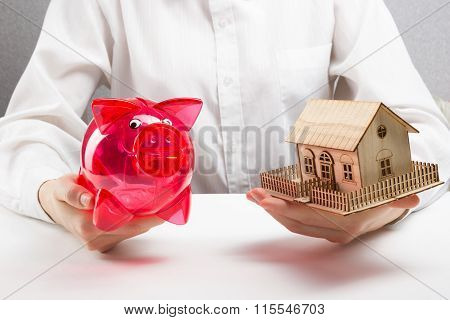 Mortgage or savings concept. hands holding money box and miniature house
