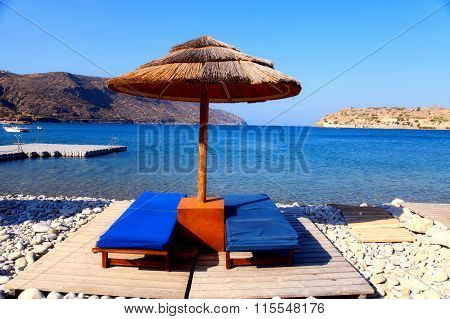 Two Lounge Chairs With Sun Umbrella On A Beach, Greece